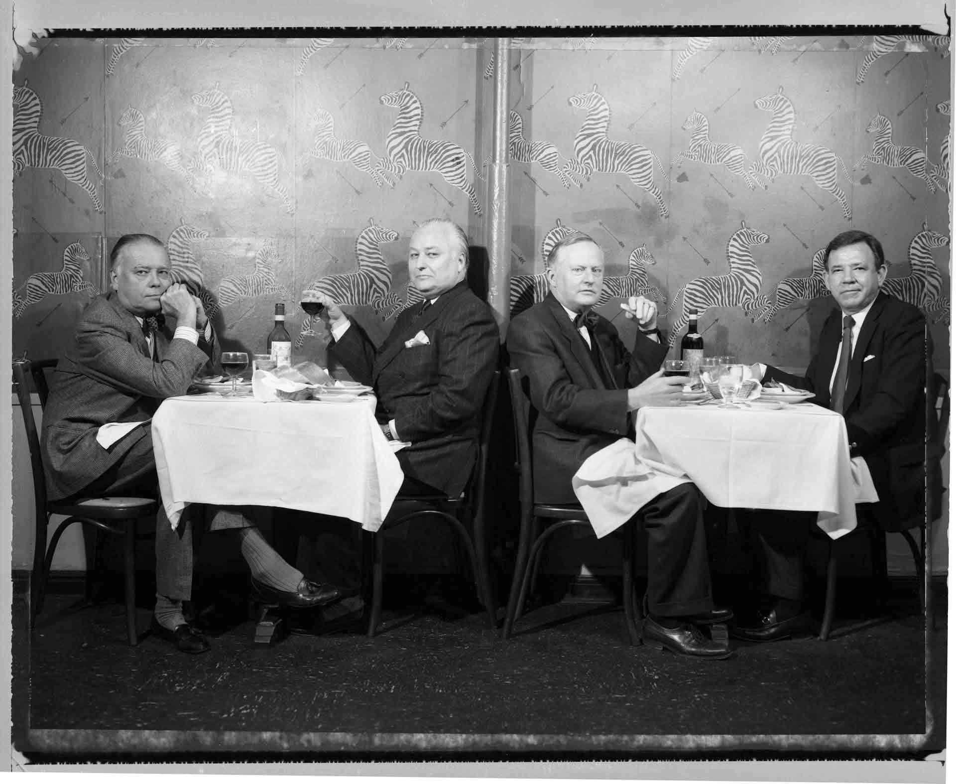 ©©Ken Shung - Four Men at Geno's. Black and white-men at dining tables, looking at the camera, restaurant, NYC