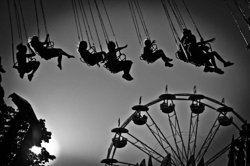 Ken Shung photography - image of people on a Ferris wheel and carousel, silhouetted against the sun, at a fairground