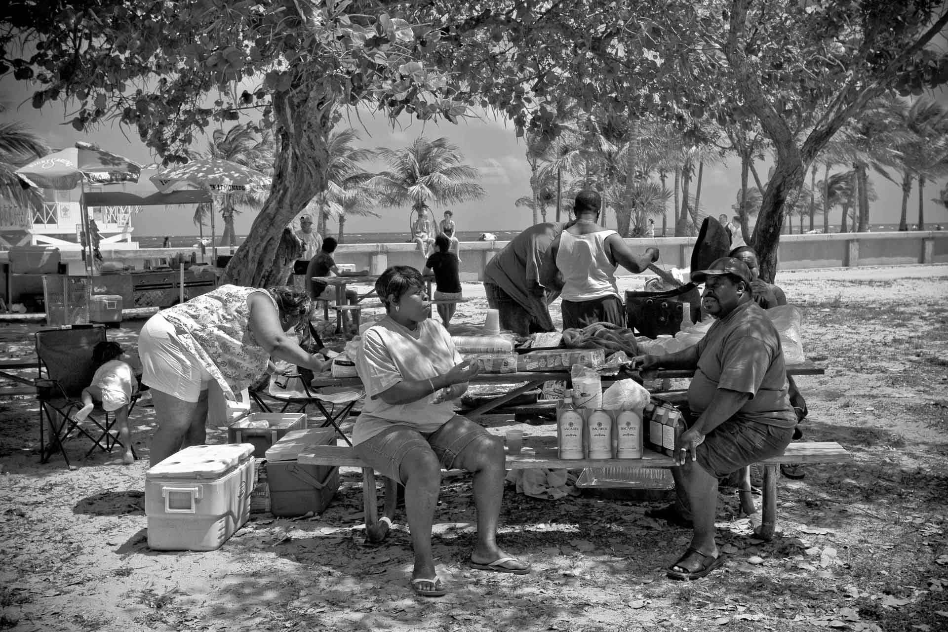 ©Ken Shung - The Picnic.black and white -group of people having a picnic, at a bench, in a park by the ocean
