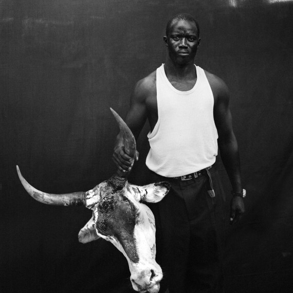 Jason Florio - Ensa with Severed Cow Head, The Gambia, West Africa. BW portrait from Makasutu series, against black cloth background