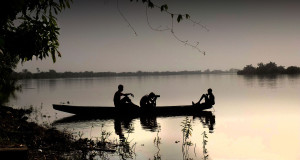 Photographer Jason Florio taking photo of a young Gambian fisherman, at dusk, in dug-out canoe , River Gambia, West Africa ©Helen Jones-Florio
