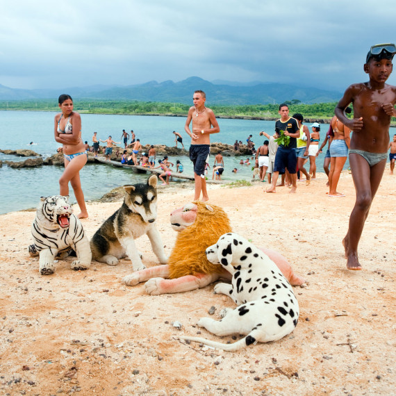 ©Jason Florio 'La Playa, Cuba'. Color - children coming from swimming, with large stuffed animals on the sand, against a blue stormy sky