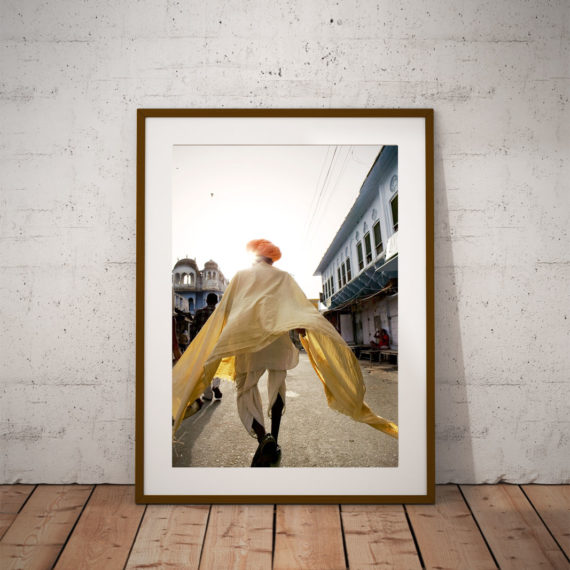 'Pushkar Man Walking' © Jason Florio - color - Indian man walks down an urban street, saffron robes flowing
