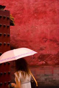 ©KEN SHUNG 'CHINESE PARASOL # 2'.color - young woman, walking with a pink parasol, vivid red background.