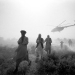 Arrival - by helicopter, Afghanistan © Jason Florio.BW image Afghan men walking away from a helicopter, taking off, in rural Afghanistan
