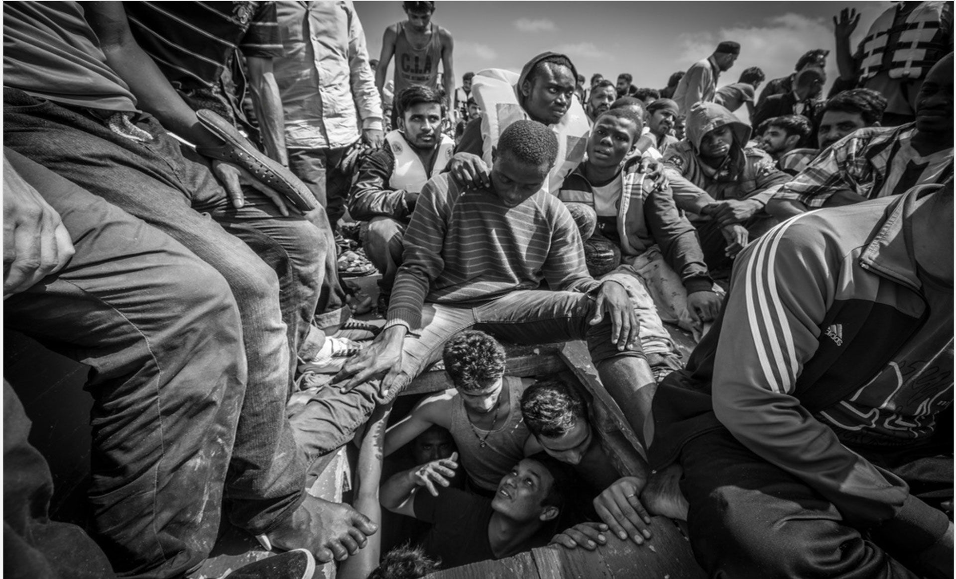 Image © Jason Florio - Photojournalism Winner, Magnum Photography Awards 2017. Migrants come from below deck on overcrowded smugglers boat