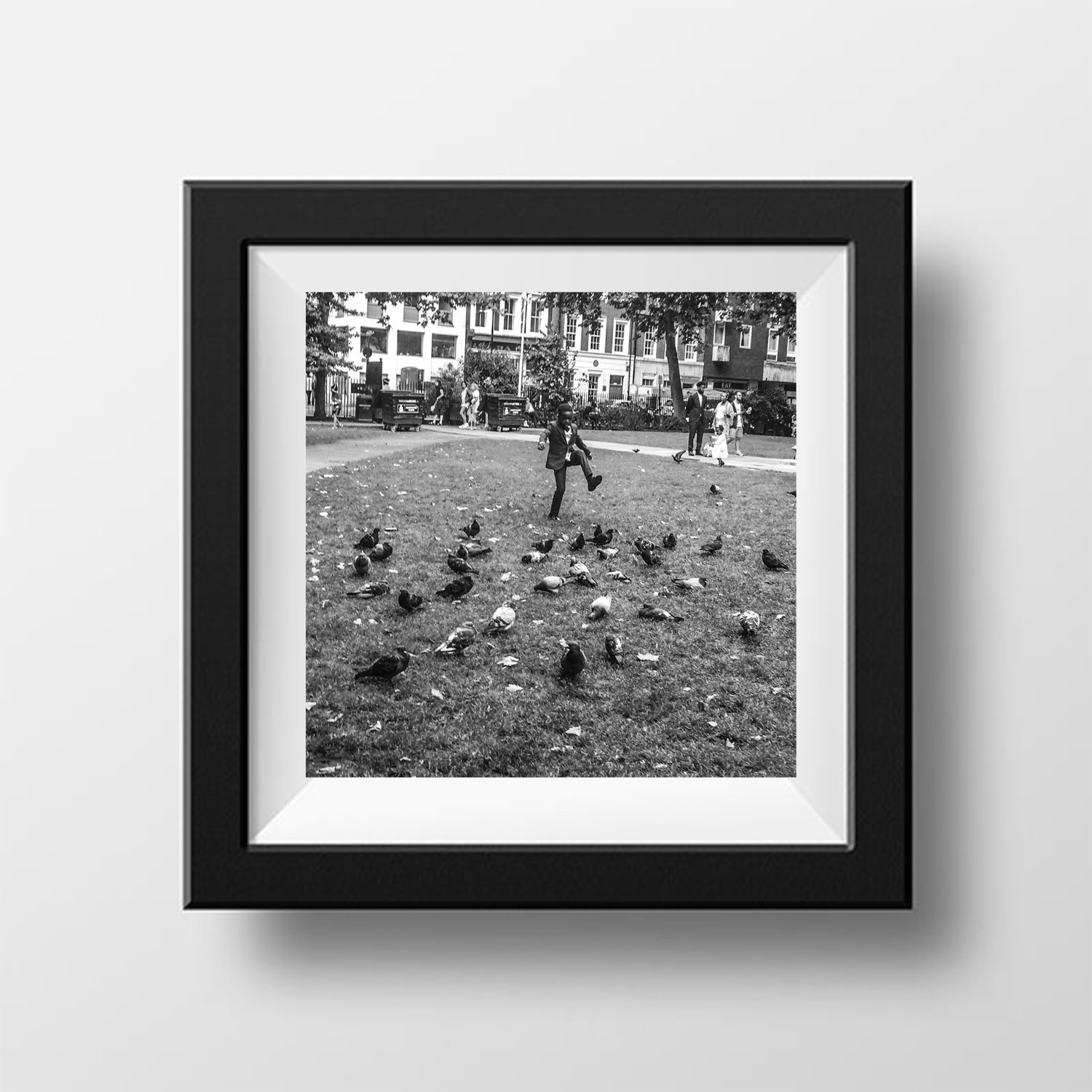 'Romper Stomper' Soho Square, London © Jason Florio. Young black boy, in a suit, stamps the ground at pigeons on the park