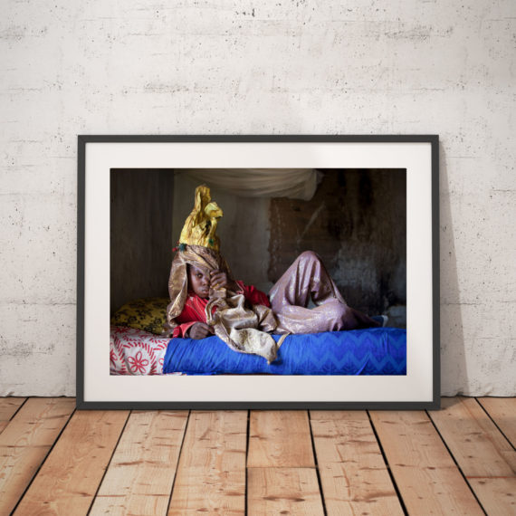 A young boy in traditional masquerade costume lounges on a bed, The Gambia, West Africa: Color photography print - 'Small Devil Masquerade' ©Jason Florio