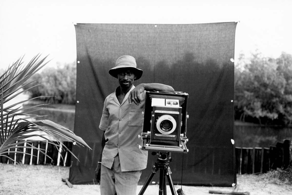 Black and white portrait - Makasutu guide, Lamin Coley, standing next to the photographer, Jason Florio's, 8x10 camera, in front of his signature black backdrop. Image ©Jason Florio