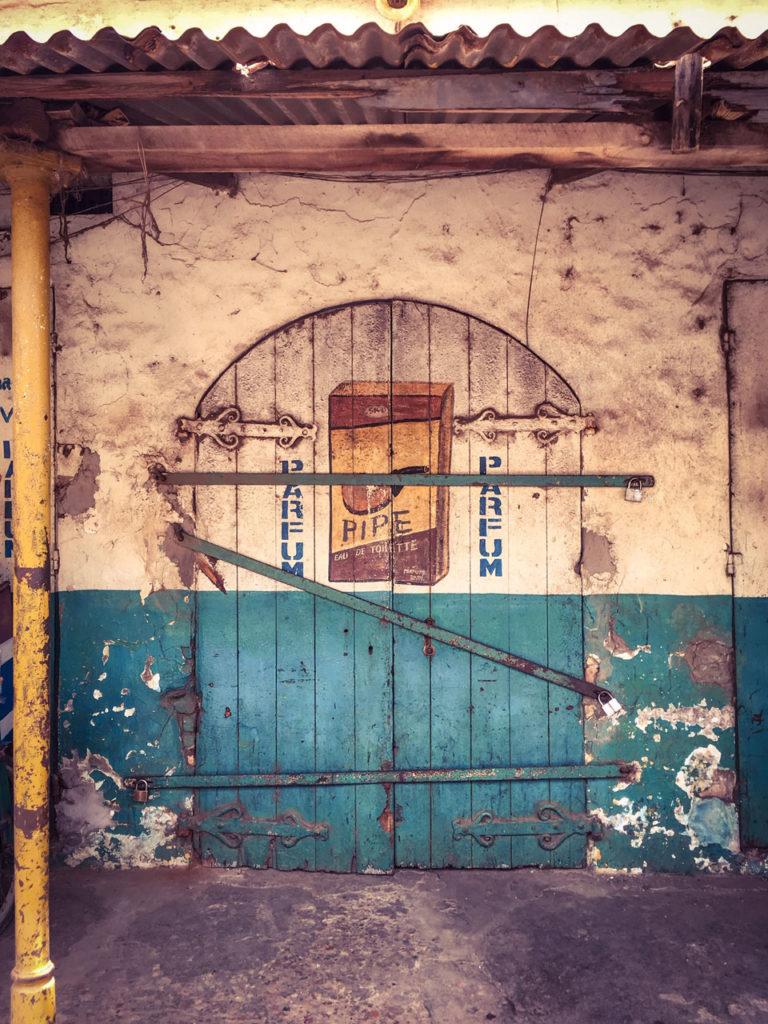 Doors - 'Pipe, eau de Toilette', decaying closed storefront, Banjul, the Gambia ©Helen Jones-Florio