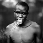 ©Jason Florio - Ismaila Smoking, The Gambia, West Africa. BW portrait from Makasutu series, against black cloth background