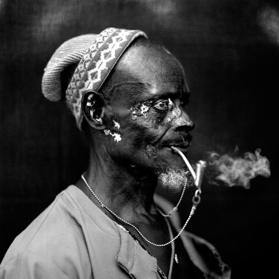 ©Jason Florio - 'Silver Pipe Man', The Gambia, West Africa. BW portrait from Makasutu series, against black cloth background