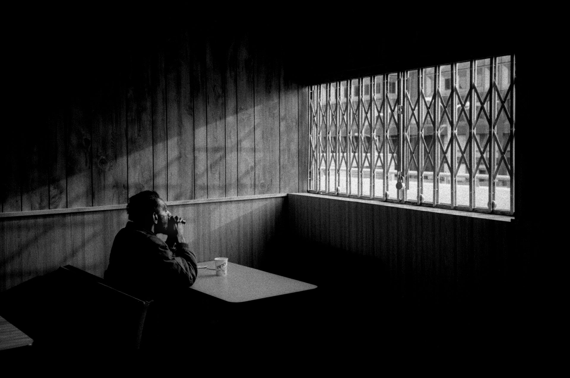 ©Robert Goldstein - .Man in Diner'. Black and White - man sits alone, staring out of a shuttered window