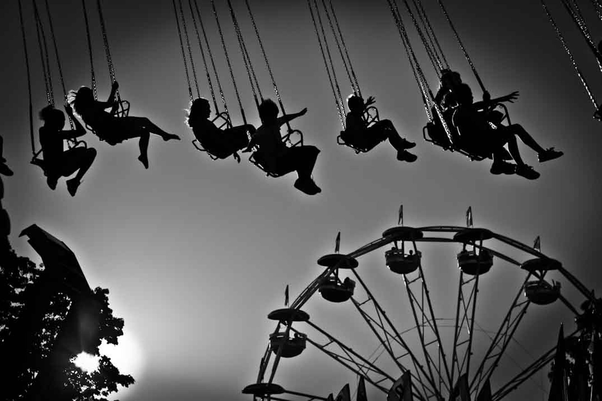 ©Ken Shung 'Swingers' . Black and white-Ferris Wheel and a carousal, fun fair, silhouetted against the sky