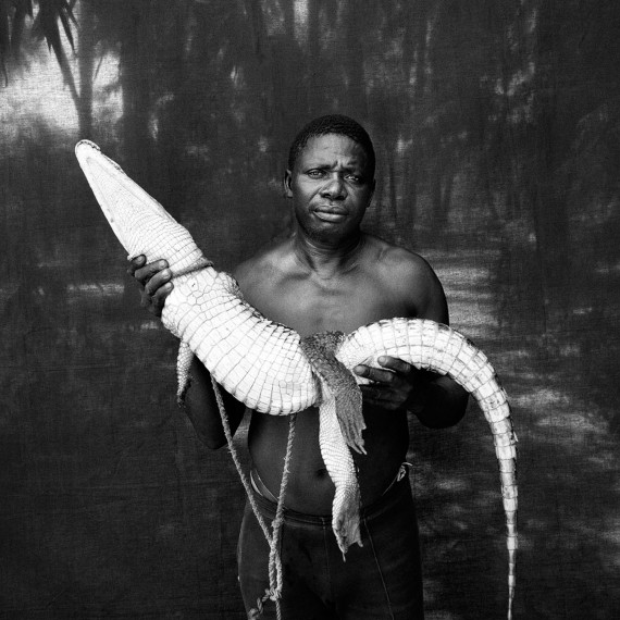 Holiday Gift Ideas - photography prints by Jason Florio -Abdou with Rescued Crocodile, The Gambia, West Africa.BW portrait from Makasutu series, against black cloth background