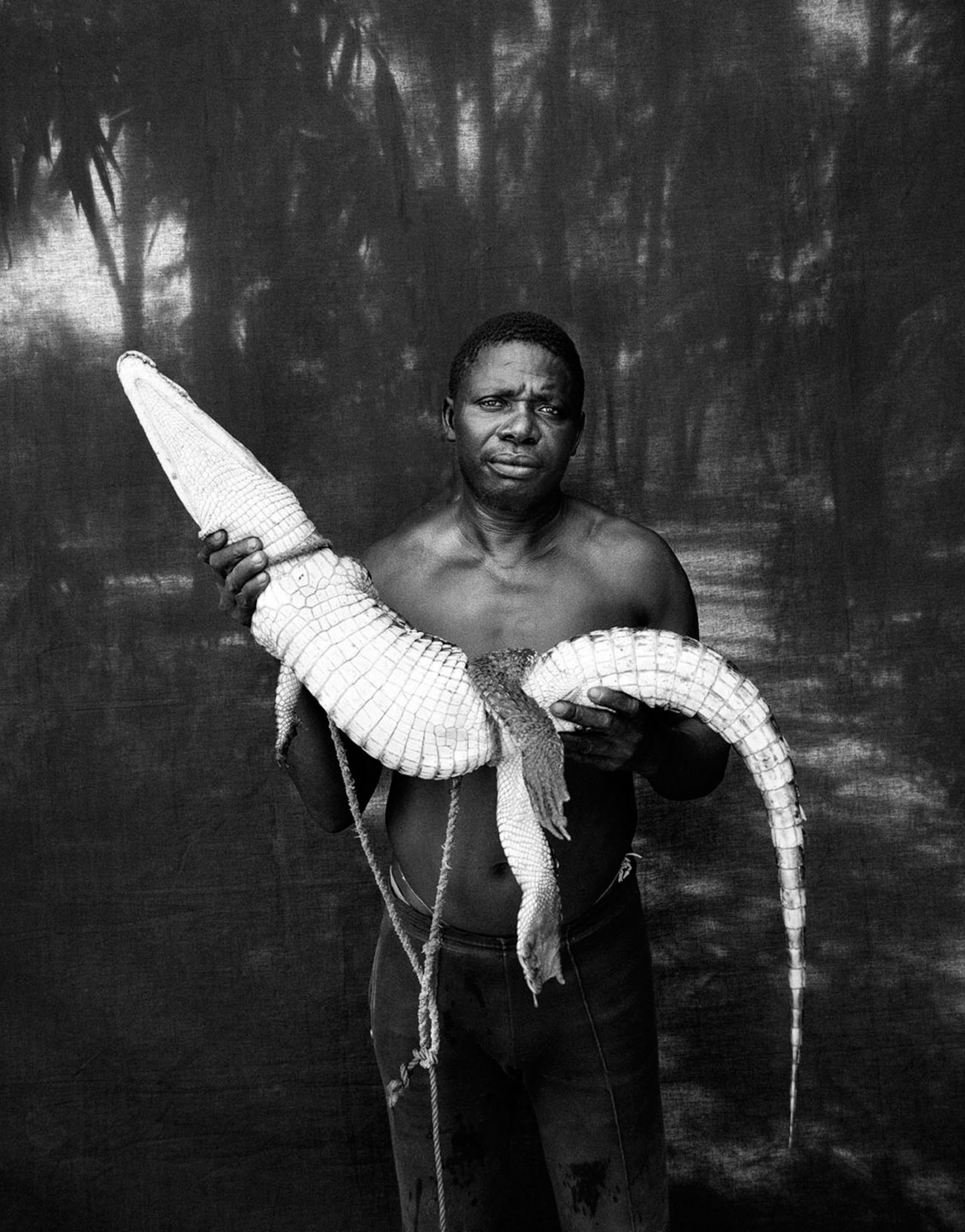 The black backdrop - Abdou with Rescued Crocodile, The Gambia, West Africa.BW ©Jason Florio -portrait from Makasutu series, against black cloth background