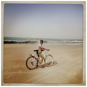 Boy Bicycle Ocean, The Gambia © Jason Florio. Color - young Gambian boy on his bicycle on a beach, West Africa