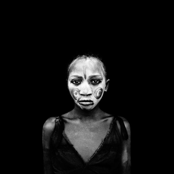 ©Jason Florio - 'Girl with Painted Face', The Gambia, West Africa. BW portrait from Makasutu series, against black cloth background