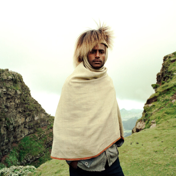 ©Jason Florio - Baboon Hat Man Ethiopia. Color - young Ethiopian man, wearing a hat made from baboon hair, stands on a cliff edge