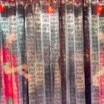 KEN SHUNG photography - image of two Chinese women in red dresses, standing behind a transparent plastic patterned curtain