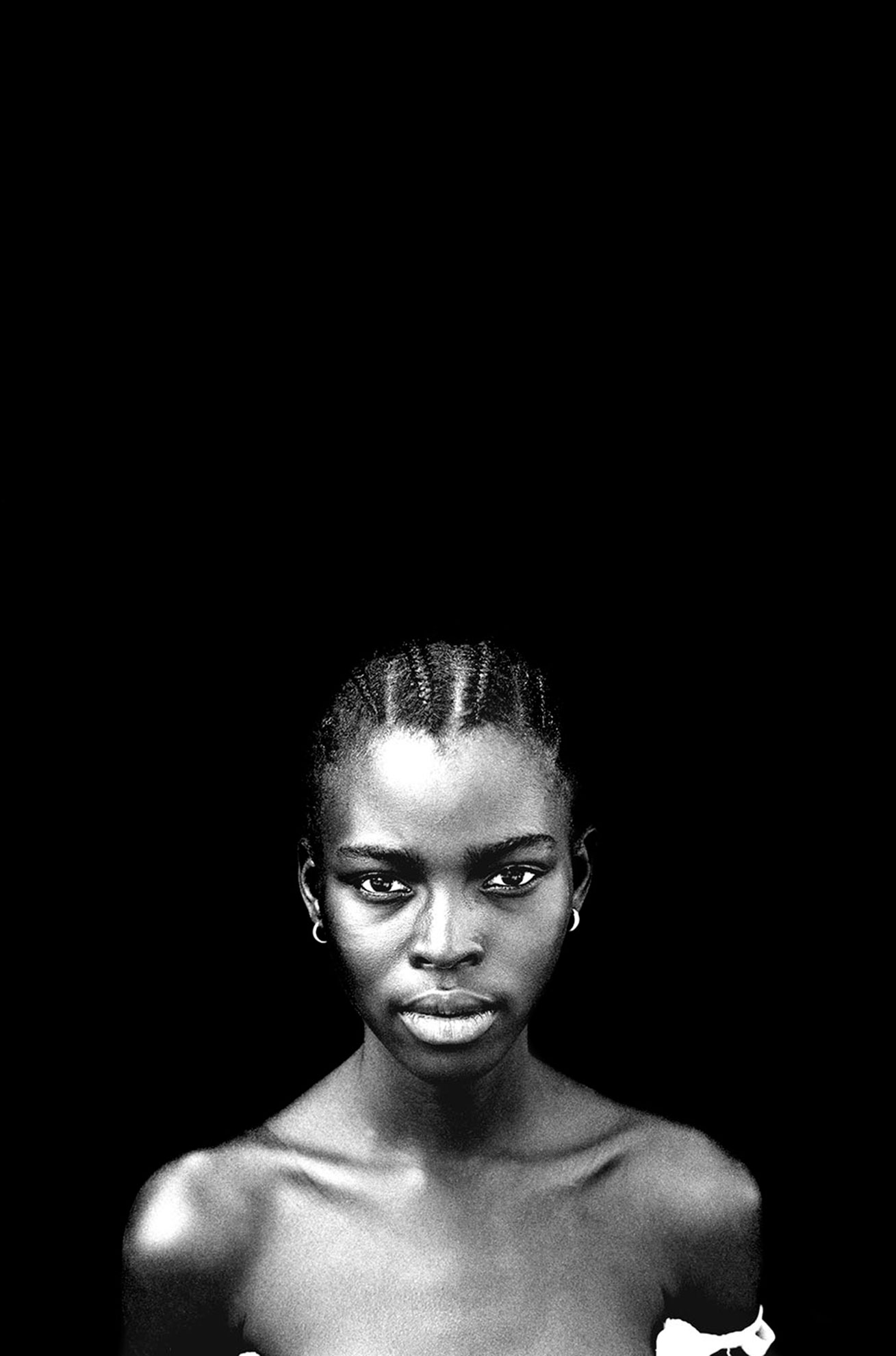 The black backdrop - 'Ida' student, The Gambia, West Africa © Jason Florio. BW portrait of young girl against black background