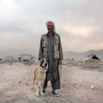 Man stands with his dog in a cemetery in Kabul, Afghanistan: Colour photography print - Afghan Fighting Dog © Jason Florio