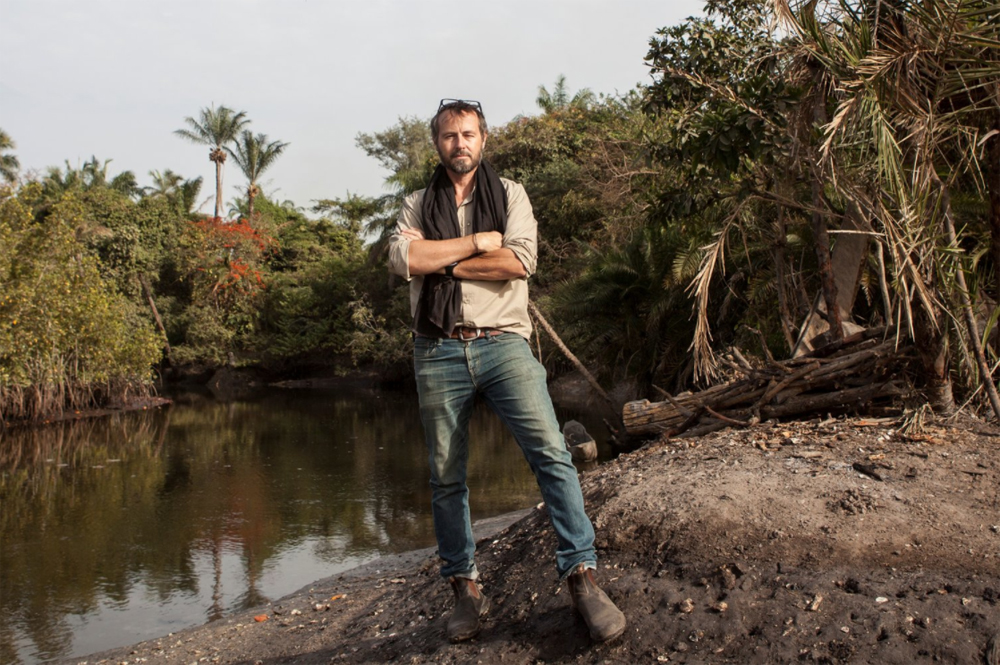 Q&A with Jason Florio, Jason Florio, the photographer stands by a river in The Gambia, West Africa - image credit: Lamin Ndong