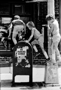 Photo of the Day - Kids playing on fire hydrant: Black and white - 'No Parking Sunday' Greenwich Village, NYC 1985 - photography prints ©Jeff Rothstein