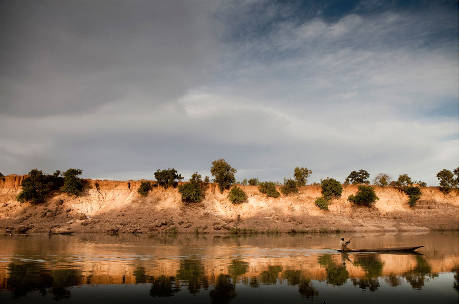 A fisherman paddles past the sandstone banks of River Gambia at Goloumbou, Senegal, West Africa. The water level in the rainy season will reach close to the top of the banks. Image ©Jason Florio - River Gambia Expedition