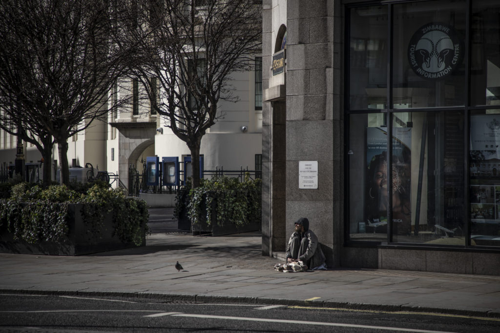 COVID 19 London lockdown. Homelessness - a lone homeless man sits on the street, Central London. Image © Jason Florio