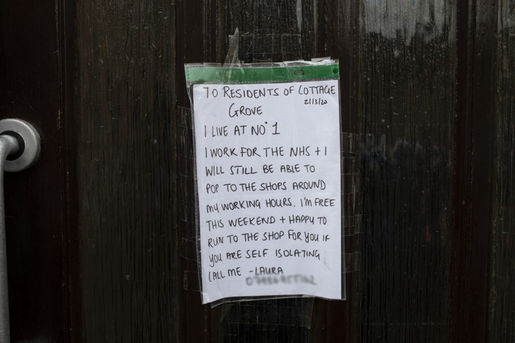 In isolation between a 'Rock and a Hot Place' - a flier on the front door of an apartment block, volunteering help with shopping for those self-isolating, UK. Image ©Jason Florio