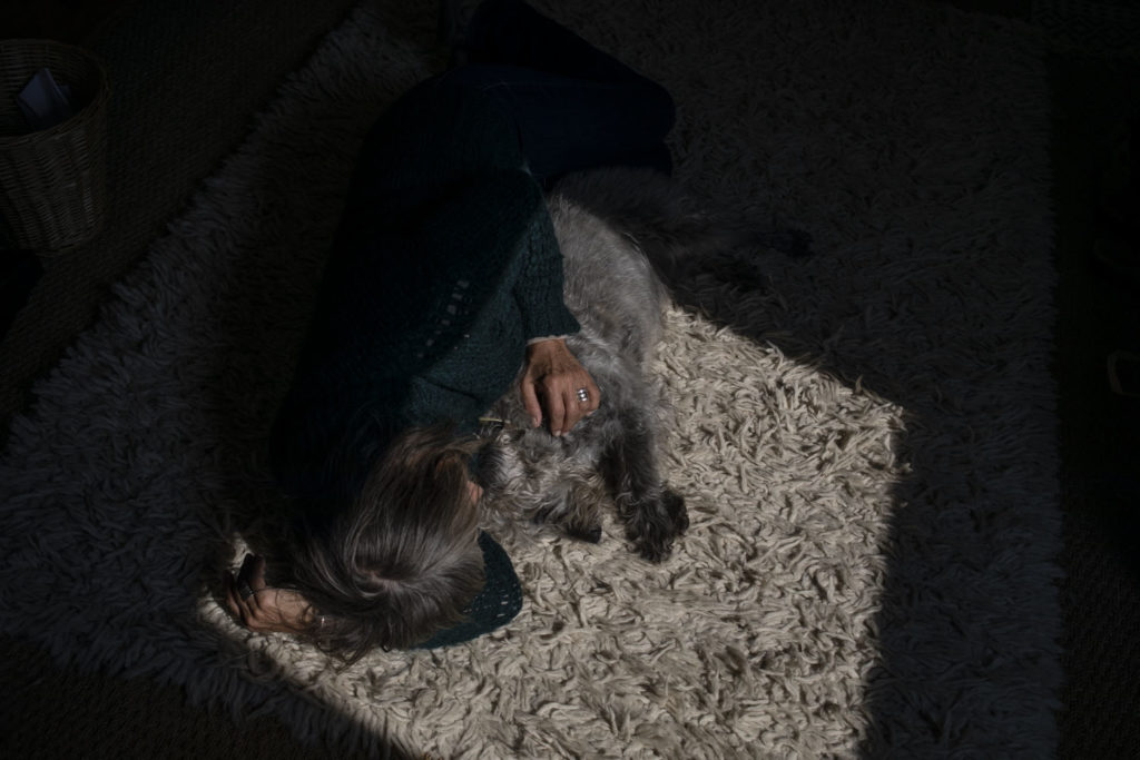 In isolation between a 'Rock and a Hot Place' - a woman lies on a carpet with a dog, half in the shadow ©Jason Florio April 2020
