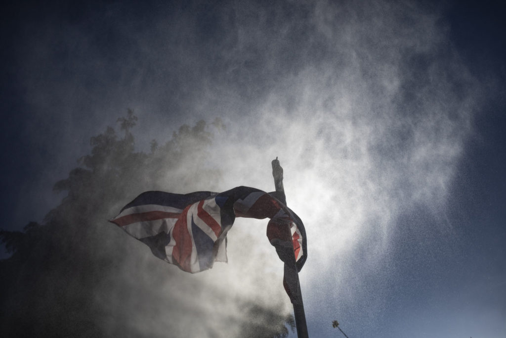 In isolation between a 'Rock and a Hot Place' - a Union Jack flag with the sun in the clouds behind it ©Jason Florio April 2020
