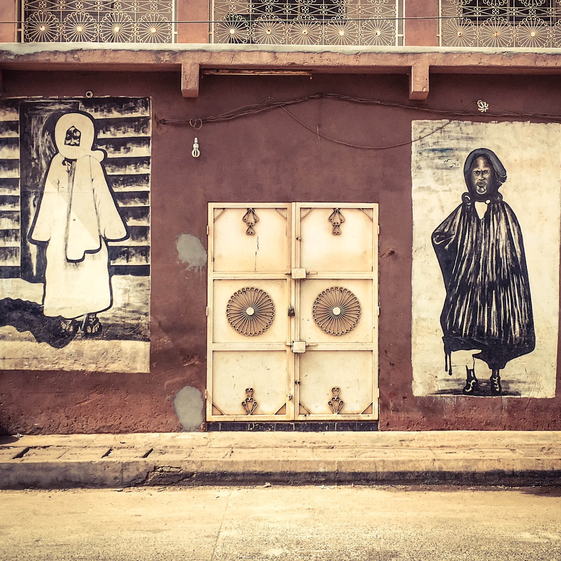 #GambiaDoors: Doors and Storefronts of The Gambia, West Africa. Mural's depicting disciples, Lamp Faal and Baye Faal, of the Mouride Sufi Brotherhood, Banjul. Image ©Helen Jones-Florio