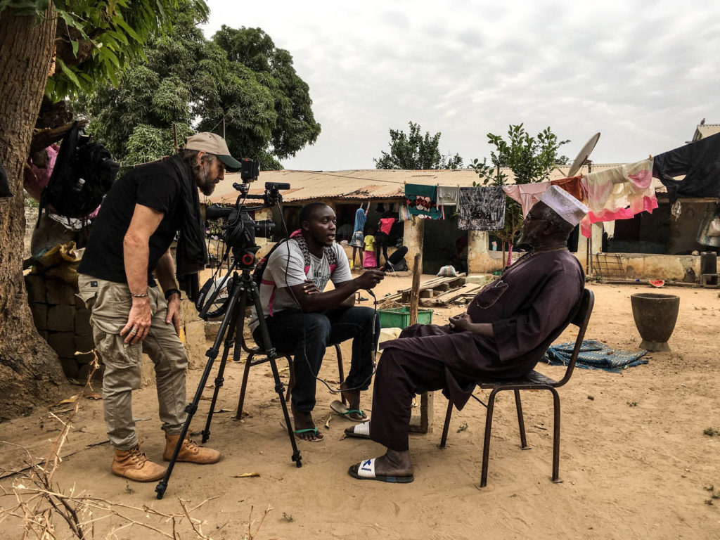 Photographer/filmmaker, Jason Florio, at work, interviewing witch hunt victims, The Gambia, West Africa. Image © Helen Jones-Florio