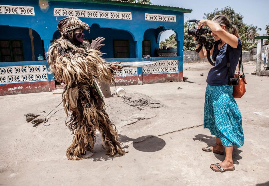Photographer/videographer, Helen Jones-Florio, films the 'Zimba', one of The Gambia's many traditional masquerades, West Africa. Image © Jason Florio