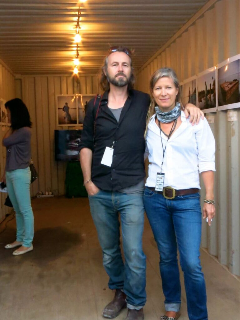 Photographers, Jason Florio and Helen Jones-Florio, standing in their 'River Gambia Expedition' exhibition container at Photoville, NYC, 2013