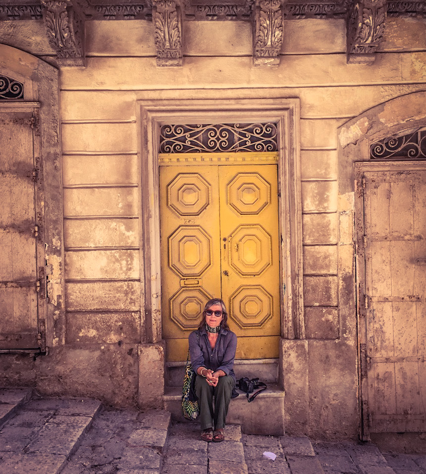 Helen Jones-Florio - founder & curator of helenjonesflorio.com gallery sits on the step of an ornate vintage door, in the streets of Valletta, Malta. Image ©Jason Florio