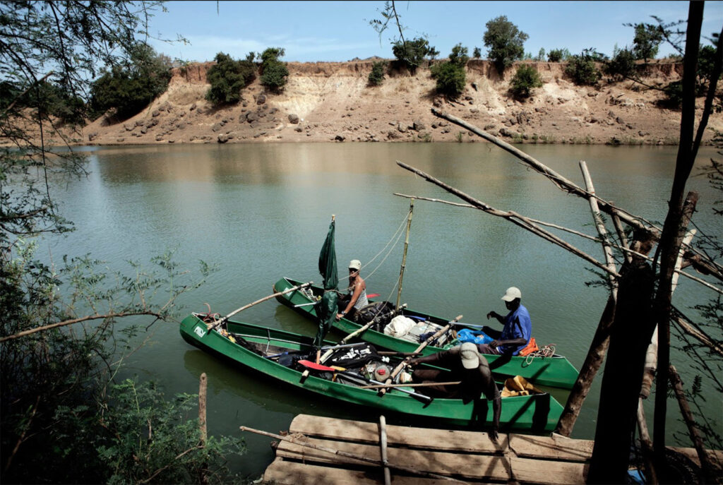 River Gambia Expedition - team members, Helen Jones-Florio, Abdou Ndong, Ebou Jarju, preparing the two canoes to paddle on the river, Senegal. Image ©Jason Florio