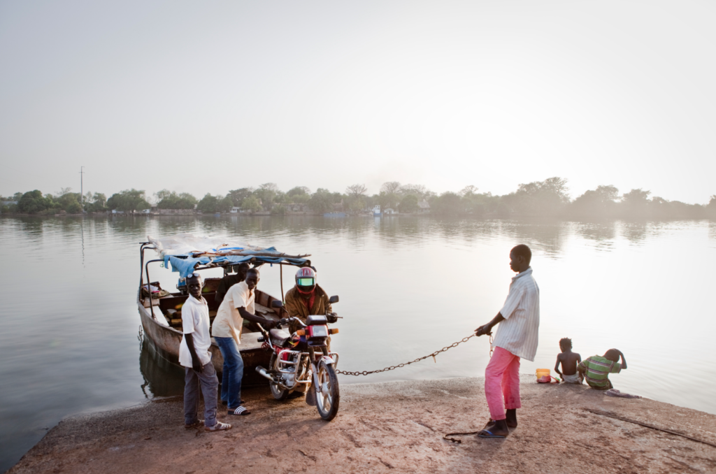 Photo Swindon International Photography Competition: Men unloading a motorcycle from a local ferry on the River Gambia, The Gambia, West Africa. Image ©Jason Florio 'River Gambia Expedition - 1044km source-sea African odyssey'