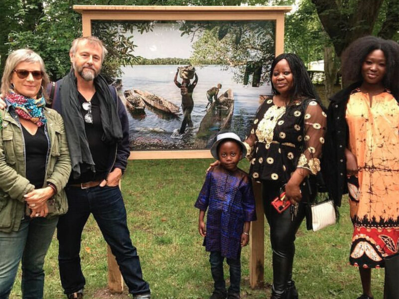@photoswindon International Photography Exhibition, 2021 - photographers and filmmakers, Helen Jones-Florio and Jason Florio standing with Gambian visitors to the exhibition in a Swindon park, in front of one of Jason Florio's River Gambia prints